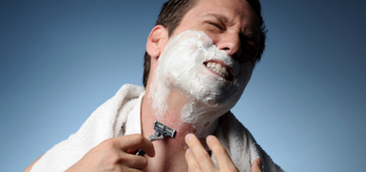 Med Shot of man shaving with razor and towel and razor burn and bumps